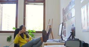 Grafico femminile che mangia caffè allo scrittorio 4k video d archivio