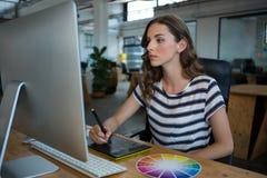 Grafico femminile che per mezzo della tavola dei grafici allo scrittorio Fotografie Stock