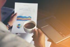 Grafico finanziario di analisi dell'uomo d'affari e tenere una tazza di caffè Fotografia Stock Libera da Diritti
