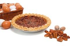 Grafico a torta di pecan con gli ingredienti su una priorità bassa bianca immagine stock