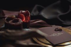 Graficzne sztuki piękne ślubu brązu i menchii karty, złoty talerz z dwa pierścionkami, świeczki dymią, tkanina, karpa na drewnie Zdjęcie Royalty Free