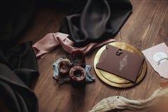 Graficzne sztuki piękne ślubu brązu i menchii karty, złoty talerz z dwa pierścionkami, świeczki dymią, tkanina, karpa na drewnie Zdjęcia Royalty Free