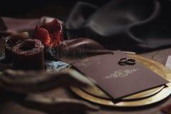 Graficzne sztuki piękne ślubu brązu i menchii karty, złoty talerz z dwa pierścionkami, świeczki dymią, tkanina, karpa na drewnie Obrazy Stock