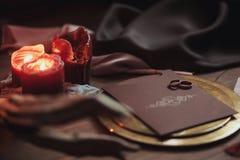 Graficzne sztuki piękne ślubu brązu i menchii karty, złoty talerz z dwa pierścionkami, świeczki dymią, tkanina, karpa na drewnie Zdjęcia Stock