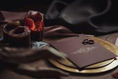 Graficzne sztuki piękne ślubu brązu i menchii karty, złoty talerz z dwa pierścionkami, świeczki dymią, tkanina, karpa na drewnian Zdjęcia Royalty Free
