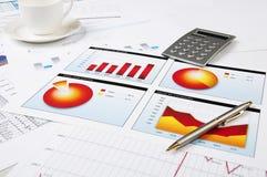 Grafieken, calculator, pen en kop van koffie Stock Fotografie