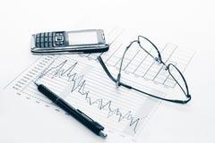 Grafieken, pen, celtelefoon en glazen stock foto's