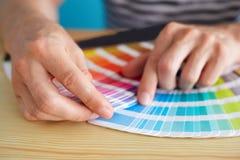 Grafikdesigner, der eine Farbe wählt Stockbild