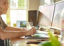 Grafikdesigner, der mit digitaler Zeichnungs-Tablette und Stift arbeitet Lizenzfreies Stockbild