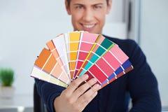 Grafikdesignerholdingfarbengebläse Stockfotografie