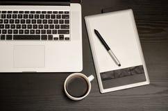 Grafiktablette mit einem Bleistift, einer Laptoptastatur und einem Tasse Kaffee auf einem schwarzen Holztisch, Abschluss oben Stockfotografie