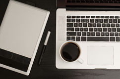 Grafiktablette mit einem Bleistift, Teil des Notizbuches und Tasse Kaffee auf einem schwarzen Holztisch Lizenzfreie Stockfotografie