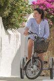 Grafische Gasse in Andros-Insel in Griechenland mit einer Frau auf ein Retro- Dreirad stockbild