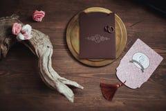 Grafische kunsten van mooie huwelijks roze en bruine kaarten, gouden plaat met twee ringen op houten achtergrond rozen, winkelhaa Stock Afbeeldingen