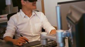 Grafische ontwerper die virtuele werkelijkheidshoofdtelefoon met behulp van terwijl het werken in bureau stock videobeelden