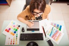 Grafische ontwerper in haar bureau Stock Foto's