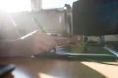 Grafische ontwerper of illustrator die een tablet en naaldpen gebruiken aan royalty-vrije stock afbeeldingen