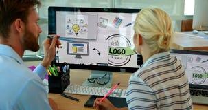 Grafische ontwerpers die over computer bij bureau werken stock videobeelden