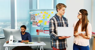 Grafische ontwerpers die over laptop in bureau bespreken stock footage