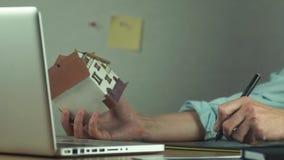 Grafisk formgivare som använder den grafiska minnestavlan som skapar byggprojekt på bärbara datorn arkivfilmer