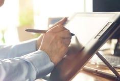 Grafisk formgivare som arbetar med den digitala teckningsminnestavlan och pennan Arkivfoton