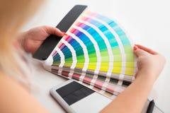 Grafisk formgivare som arbetar på en digital minnestavla och med pantone royaltyfri fotografi