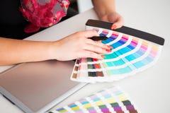 Grafisk formgivare som arbetar på en digital minnestavla och med pantone Arkivfoton