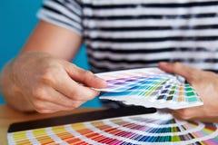 Grafisk formgivare som väljer en färg royaltyfri foto