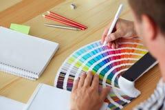 Grafisk formgivare som väljer en färg Arkivbild