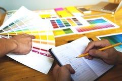 Grafiska formgivare väljer färger från färgmusikbandprövkopiorna för fotografering för bildbyråer