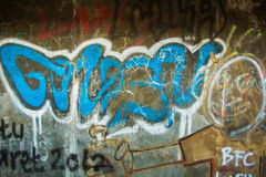 Grafiti sbiadito sulla parete incrinata del cemento Immagine Stock