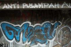 Grafiti sbiadito sulla parete incrinata del cemento Fotografie Stock