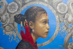 Grafitti av en flicka med en röd prydnad i hennes hår på en blå bakgrund med gråa modeller royaltyfria foton