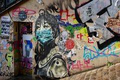 Grafitti av flickan i facemask på den Paris gatan royaltyfri bild