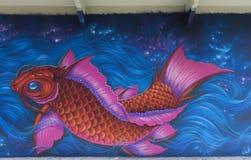 Grafitti av rosa färgfisken i blått vatten Arkivbild