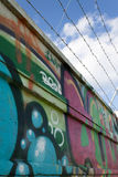 Grafitti and barbwire. Barbwired wall covered with graffiti and a beautiful sky stock images