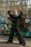 Grafitti behind a gate. Woman standing behind a park gate in front of a grafitti wall Royalty Free Stock Photos