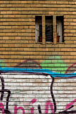 Grafitti on the bricks. Grafitti on a wall in bricks with a small window Royalty Free Stock Images