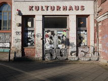 Grafitti covering front of small storefront. With peeling facade during early morning light in German city Stock Photos