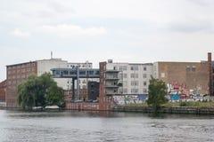 Grafitti-målade tegelstenbyggnader nära festfloden i Kreuzberg, Berlin arkivbild