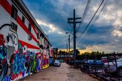 Grafitti och parkerade bilar i en gränd på solnedgången i Baltimore, Mars royaltyfria foton