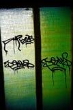 Grafitti på en glass dörr. Arkivbild