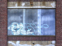 Grafitti på fönster av övergiven byggnad Arkivfoto