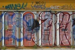 Grafitti på plast- toalettdörrar Arkivfoto