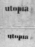 Grafitti på sidan av väggen som påstår, två gånger, `-utopi`, Arkivbild
