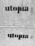 Grafitti on side of wall stating, twice, `Utopia`. `Utopia` graffiti spray painted on the side of a wall stock photography
