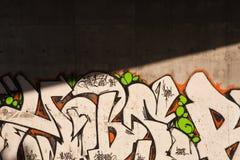 Grafitti. Urban grafitti on a concrete wall split with sunshine and shade Royalty Free Stock Image