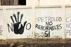 Grafitti on a wall near petroleum depots Lanzarote, spain. Lanzarote / Spain - 04/03/2016: Anti fossil-fuel graffiti is written on a wall near oil and gas stock photography