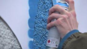 Grafittikonstnär i gatan som gör konst genom att använda sprutmålningsfärg och stencilen Stencilgatakonst, stads- kultur lager videofilmer