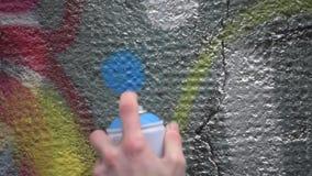 Grafittikonstnär i gatan som gör konst genom att använda sprutmålningsfärg på betongväggen Gatakonst, stads- kultur lager videofilmer